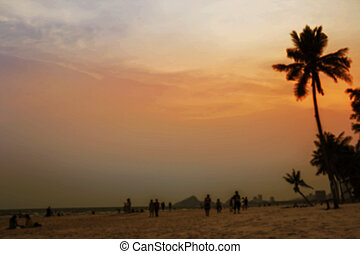 Abstract blurred background of people relaxing on the beach at twilight