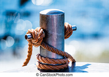 Abstract: Rope tied in a knot on a bollard. Mooring rope wrapped around the cleat on sea background. Metallic capstan in harbor for the mooring of yachts and boats. Blurred background.