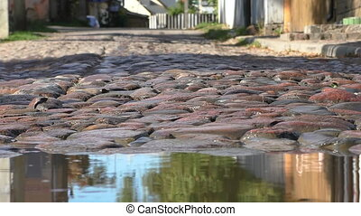 Abstract cars cobblestone street - Close up of a puddle on...