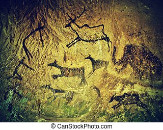 Abstract children art in sandstone cave. Black carbon paint ...