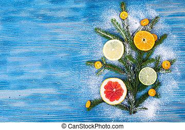 Abstract Christmas tree food background with grapefruit, mandarin, lemon, lime, kumquat