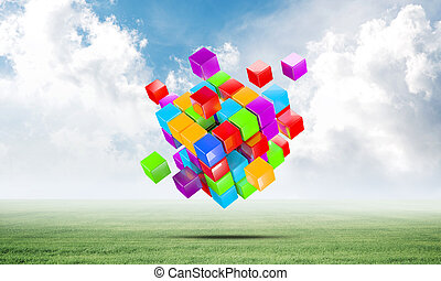 Abstract colorful cubes on green meadow