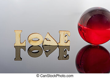 Abstract composition of love. Isolated wooden letters and glass balls.