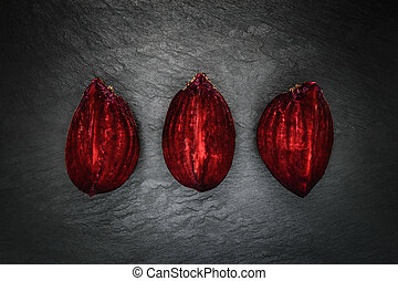 Abstract composition of three pieces beetroot placed in line on black stone background surface