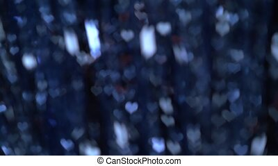 Abstract dark blue christmas garland lights in the shape of hearts blurry bokeh background