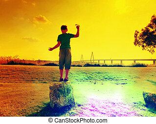 Abstract effect. Blond hair boy is playing on sea side. Big traffic bridge between islands