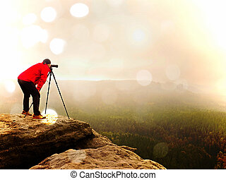 Abstract effect. Nature photographer prepare camera to takes impressive photos of misty fall landscape
