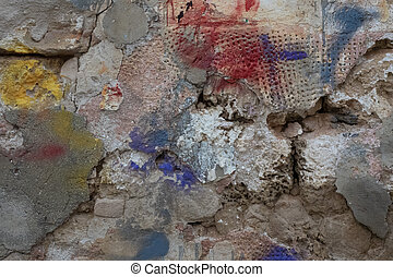 Abstract grunge background of old half-ruined stone wall, with spots of red, blue and yellow paint.
