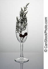 Abstract holiday background with a champagne glass with a coniferous branch on a light background.