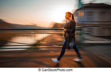 woman walking down the street in morning sun light -...