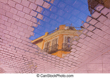 Abstract mirror images of a building in a puddle