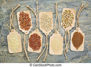 abstract of healthy, gluten free grains (quinoa, sorghum, brown rice, teff, buckwheat, amaranth, millet) - top view of paper price tags against a slate stone