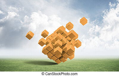 Abstract orange cubes on green meadow