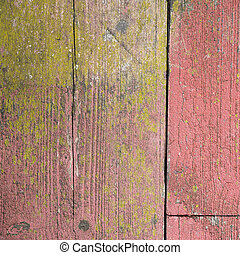old peeling red paint on grungy planks with moss