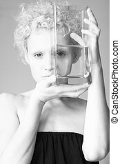 Abstract picture - the girl looks through the empty glass, black and white photo.