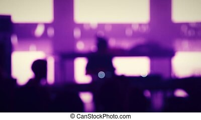 Blurred Silhouette of the Raving Crowd and the DJ Playing in Front of Bright LED Displays with VJing in the Night Club