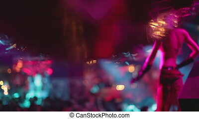 abstract shot of in a nightclub, shot close to a glitterball, with a blurred gogo dancer in the background