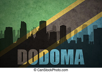 abstract silhouette of the city with text Dodoma at the vintage tanzanian flag background