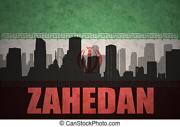 abstract silhouette of the city with text Zahedan at the vintage iranian flag background