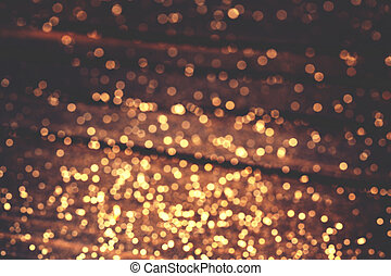 Abstract sparkling background with golden round lights over dark backdrop