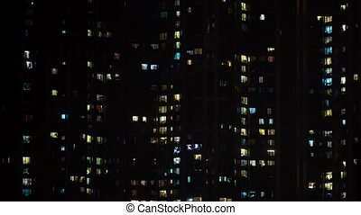 Abstract time lapse of apartment block at night.