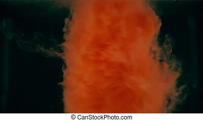 Abstract twirl of orange liquid paint dissolving in water
