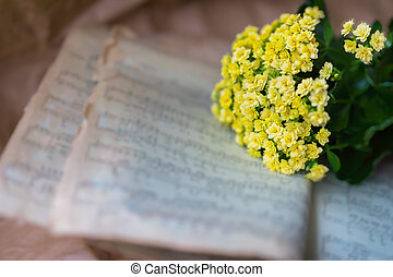 Abstract vintage grunge music background yellow flowers on yellowed old music book with worn paper. Concept of romantic melody, forgotten and unforgotten past
