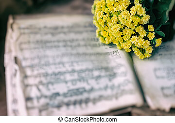 Abstract vintage music background yellow flowers on yellowed music book with worn paper, antique music sheet. Concept of romantic melody, forgotten, unforgotten past