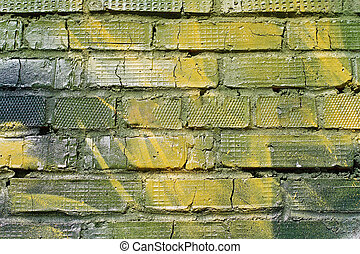 Abstract yellow-green brick wall with cracks as background, texture