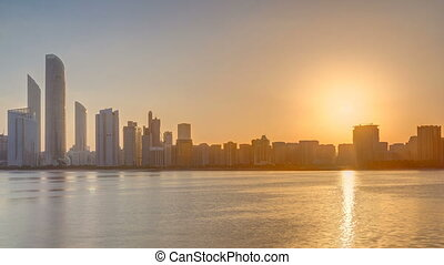 Abu Dhabi city skyline on sunrise time with water reflection timelapse.
