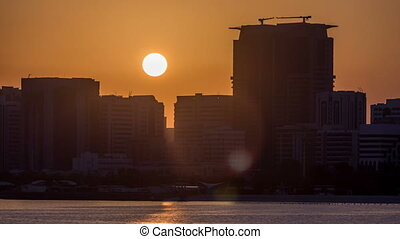 Abu Dhabi city skyline on sunrise time with water reflection...