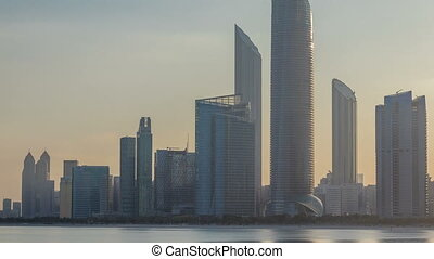 Abu Dhabi city skyline with skyscrapers after sunrise with water reflection timelapse