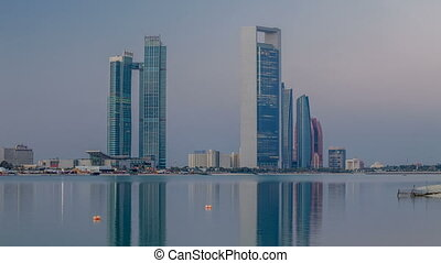 Abu Dhabi city skyline with skyscrapers before sunrise with...