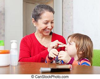 abuela, poniendo, facepowder, en, niña