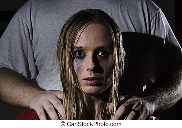 portrait of an abused woman with untidy hair and smudged makeup with a man standing behind her holding his hands on her shoulders cropped horizontally
