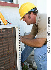 AC Repairman - An air conditioning tech working on a...