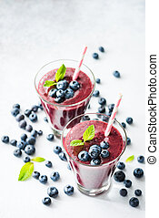 Acai blueberry smoothie in glass with drinking straw on...