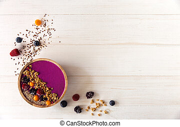 Acai smoothie, granola, seeds, fresh berries in a wooden bowl. Plate filled with berries on white wooden background. Overhead, top view, flat lay