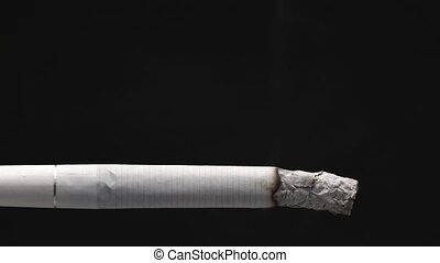 Accelerated video of a burning cigarette on a black background close-up. Timelapse video footage.