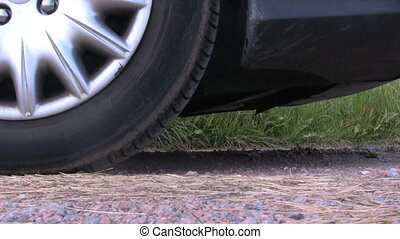 The skidding wheel of an accelerating car on a gravel road