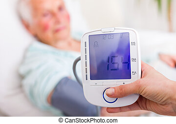 Caregiver measuring elderly woman's systolic blood pressure in hospital.