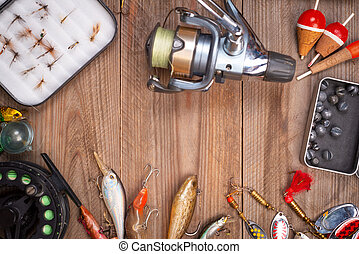 Accesories for fishing on wooden background with copyspace.