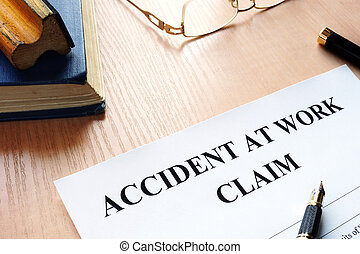 Accident at work claim and glasses on a table.