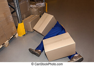 Accident at work - Warehouse worker lying under cardboard...