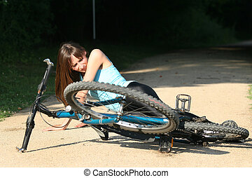Female bike rider takes a tumble and lying in pain on the road