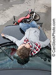 Accident - Motorcyclist is being hit by a car, and lies...