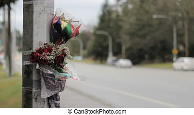 Accident Scene Memorial - Flowers are taped against a light...
