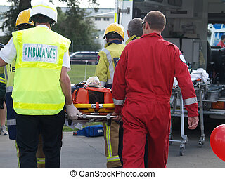 The paramedics & fireman carrying an accident victim past the ambulance to a waiting Helicopter. A simulated training exercise.