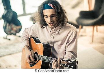 Good-looking young singer in bright bandana having musical hobby