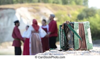 Accordion close up, on the background of a group of young people doing round dance in Russian national costumes